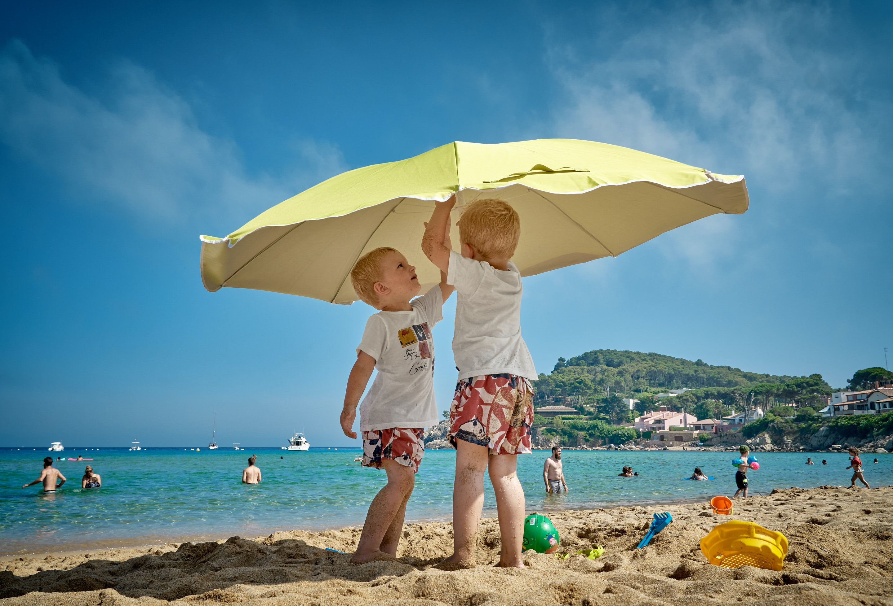 two children playing under umbrella on seashore