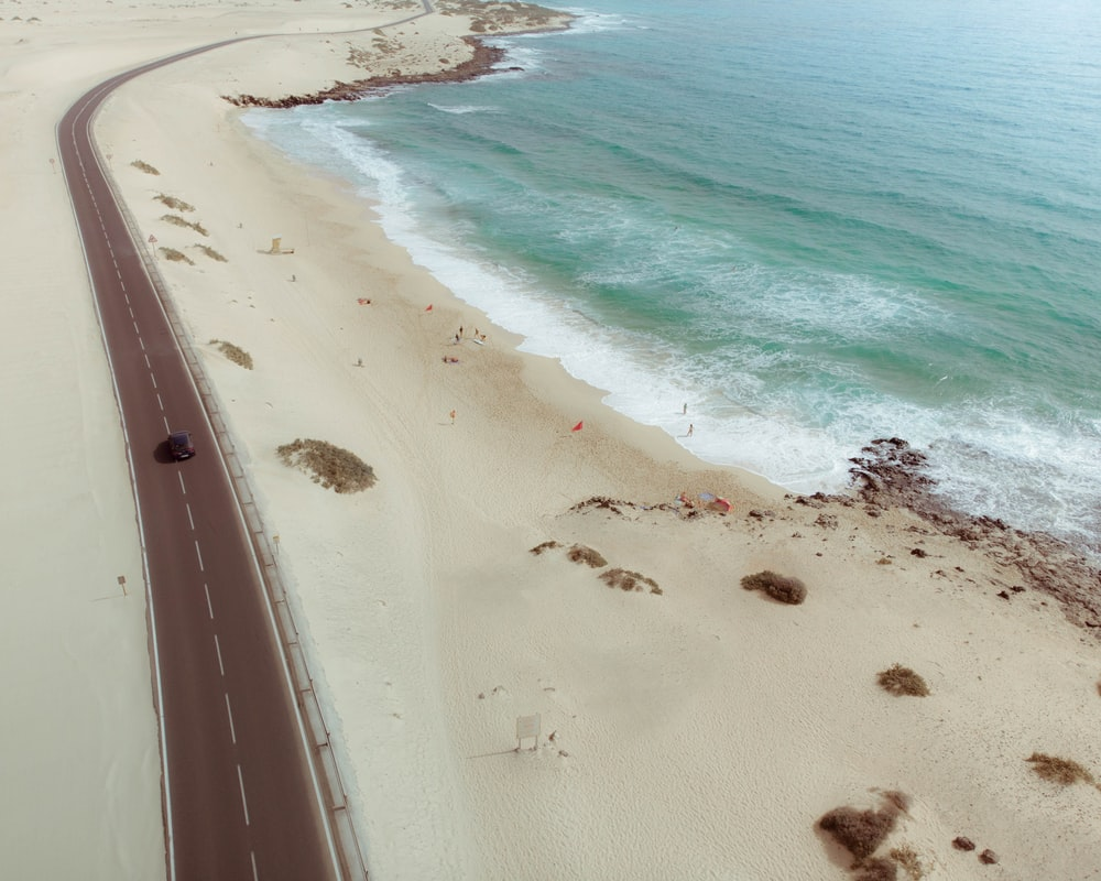 aerial photo of black vehicle moving towards near shoreline at daytime