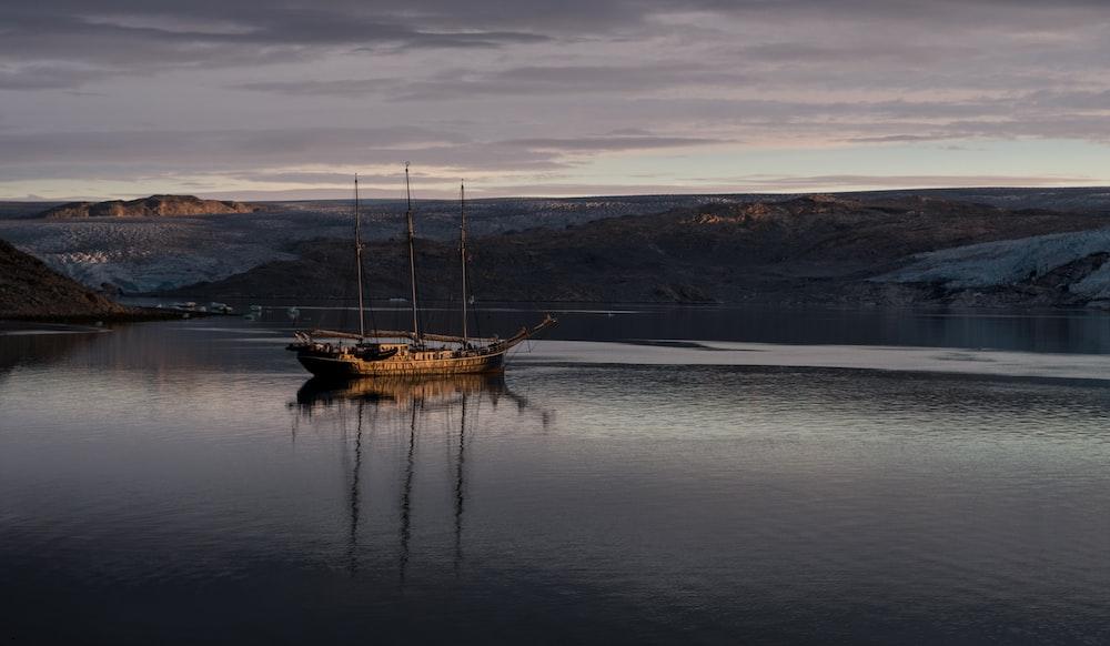 gray sailboat near island