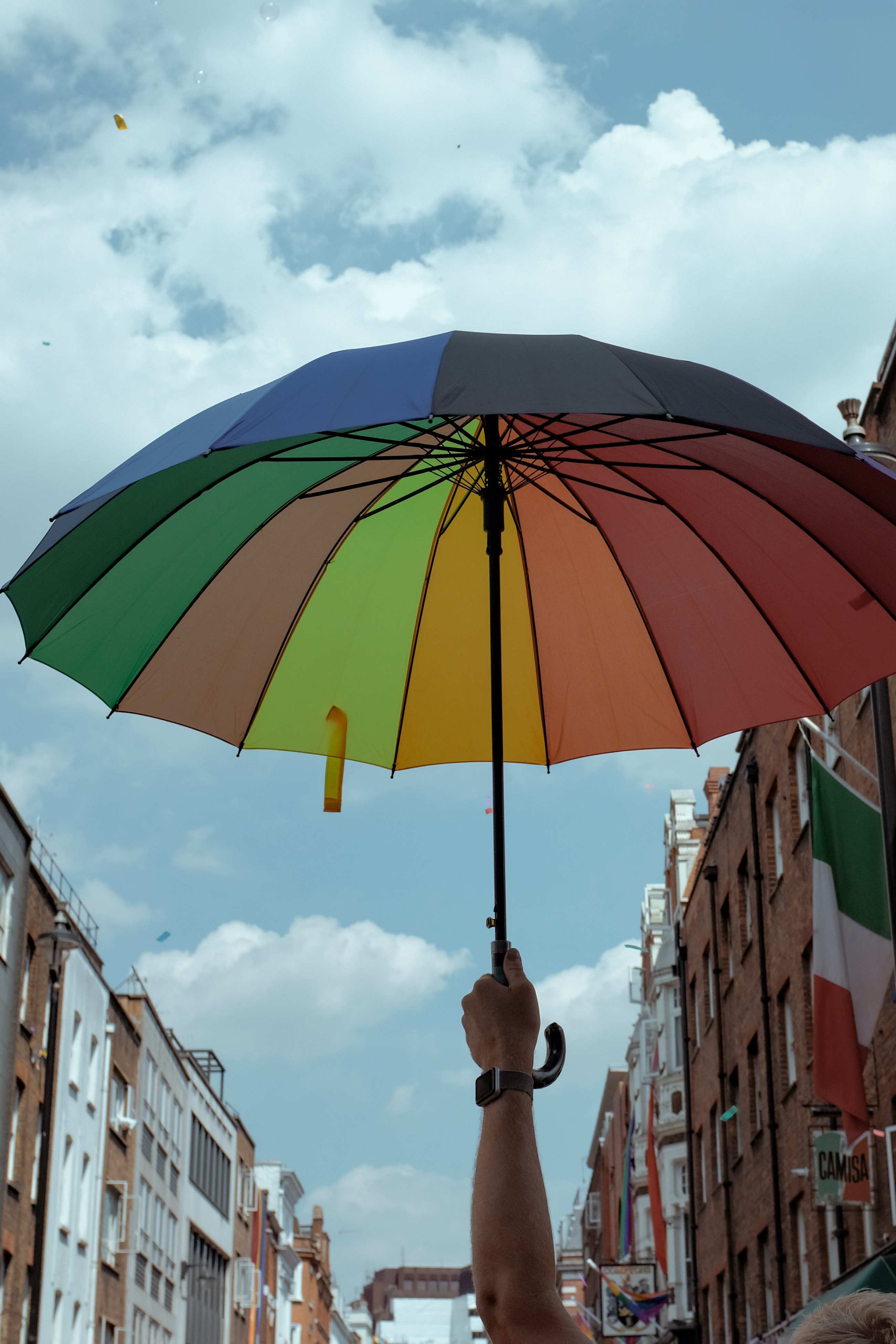 man holding multicolored classic umbrella