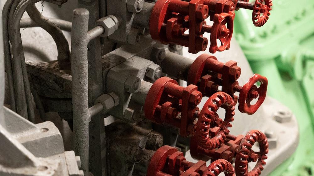closeup photo of gray and red metal machine