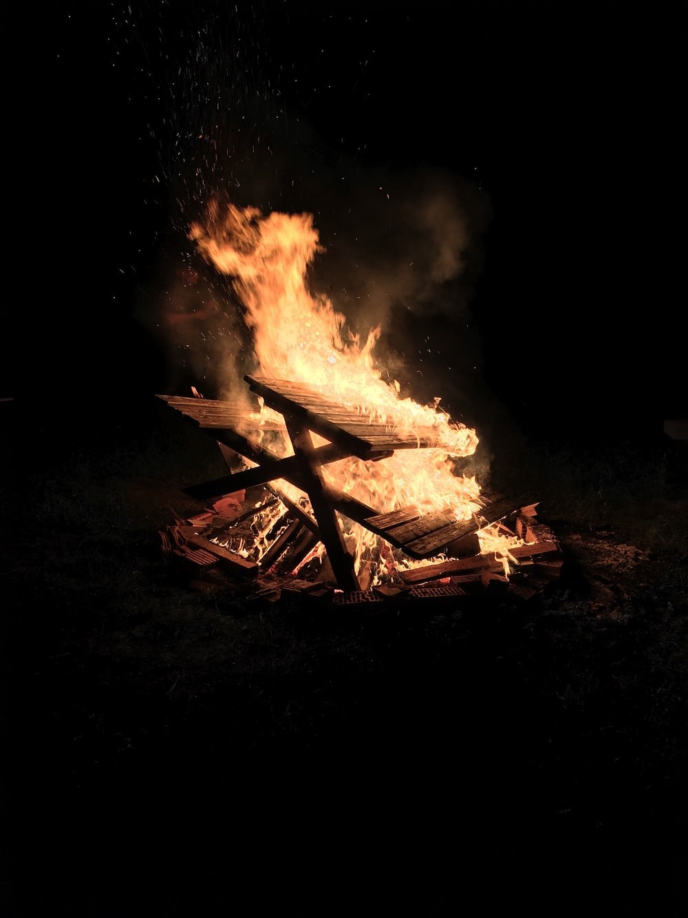 picnic bench on fire against black background