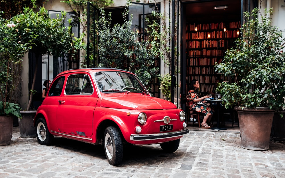 red 3-door hatchback parked outside establishment
