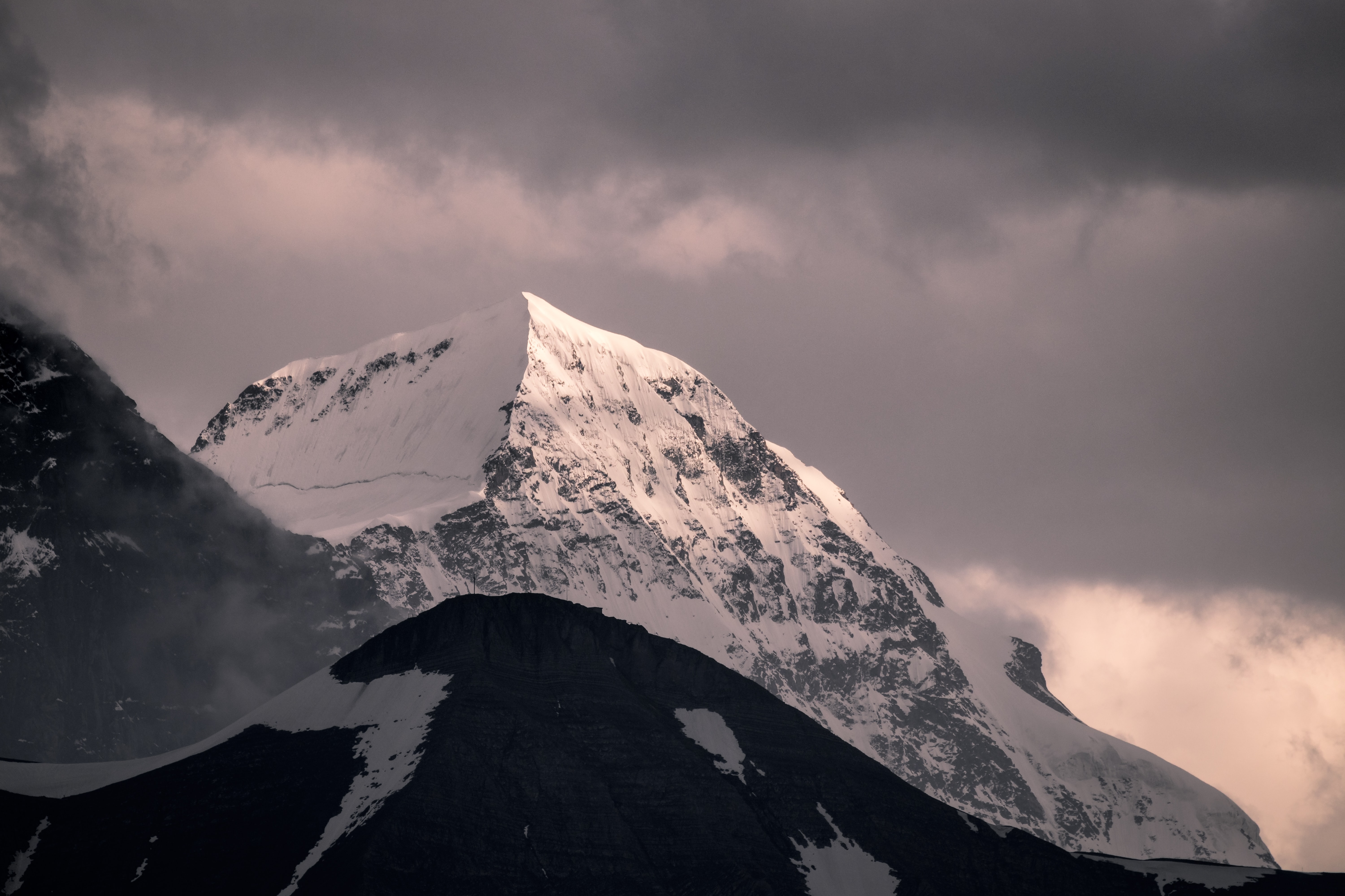 mountain covered by snow under white clouds at daytime