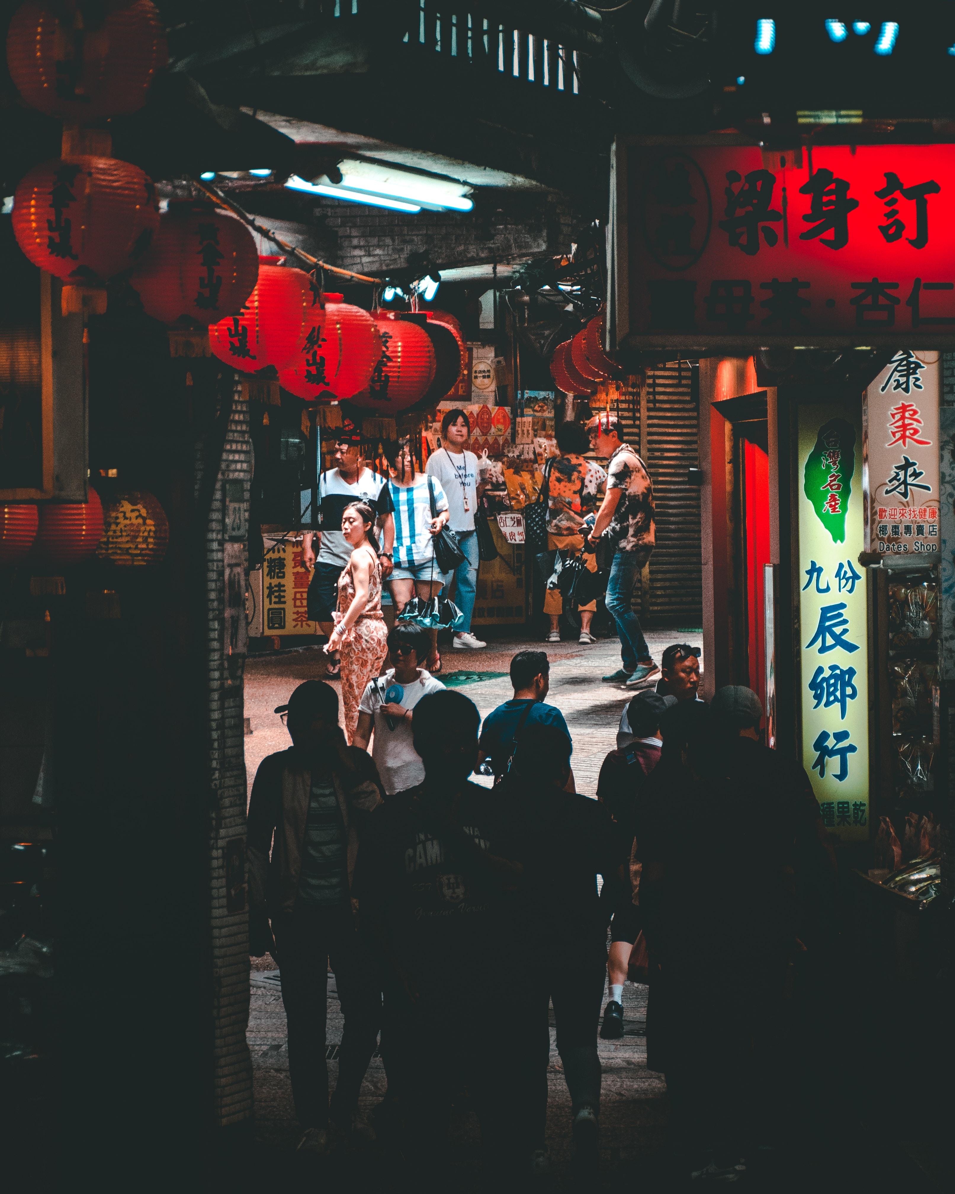 people walking on pathway between stores