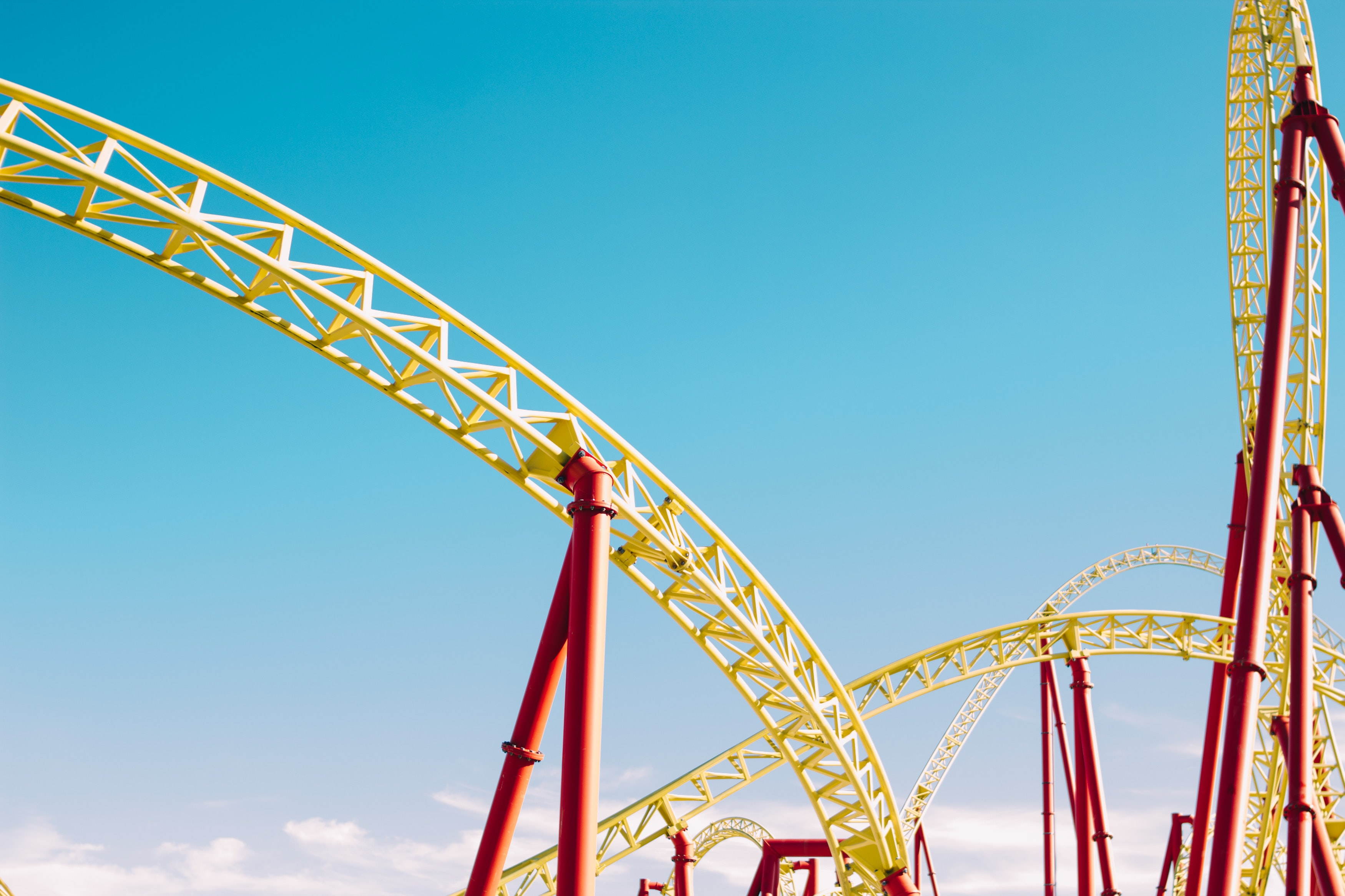 yellow and red roller coaster under blue sky at daytime