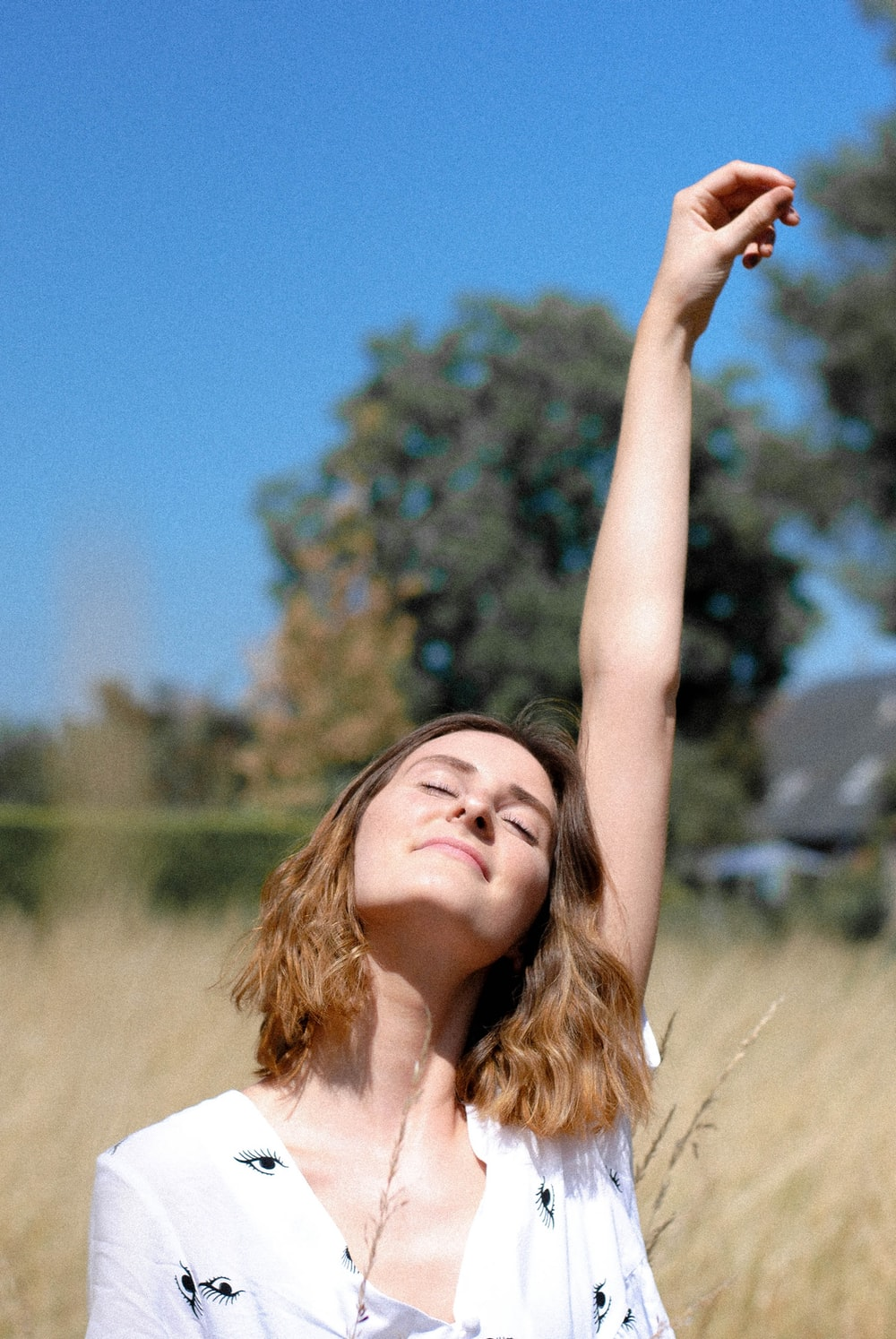 woman rising her left hand on wheat field