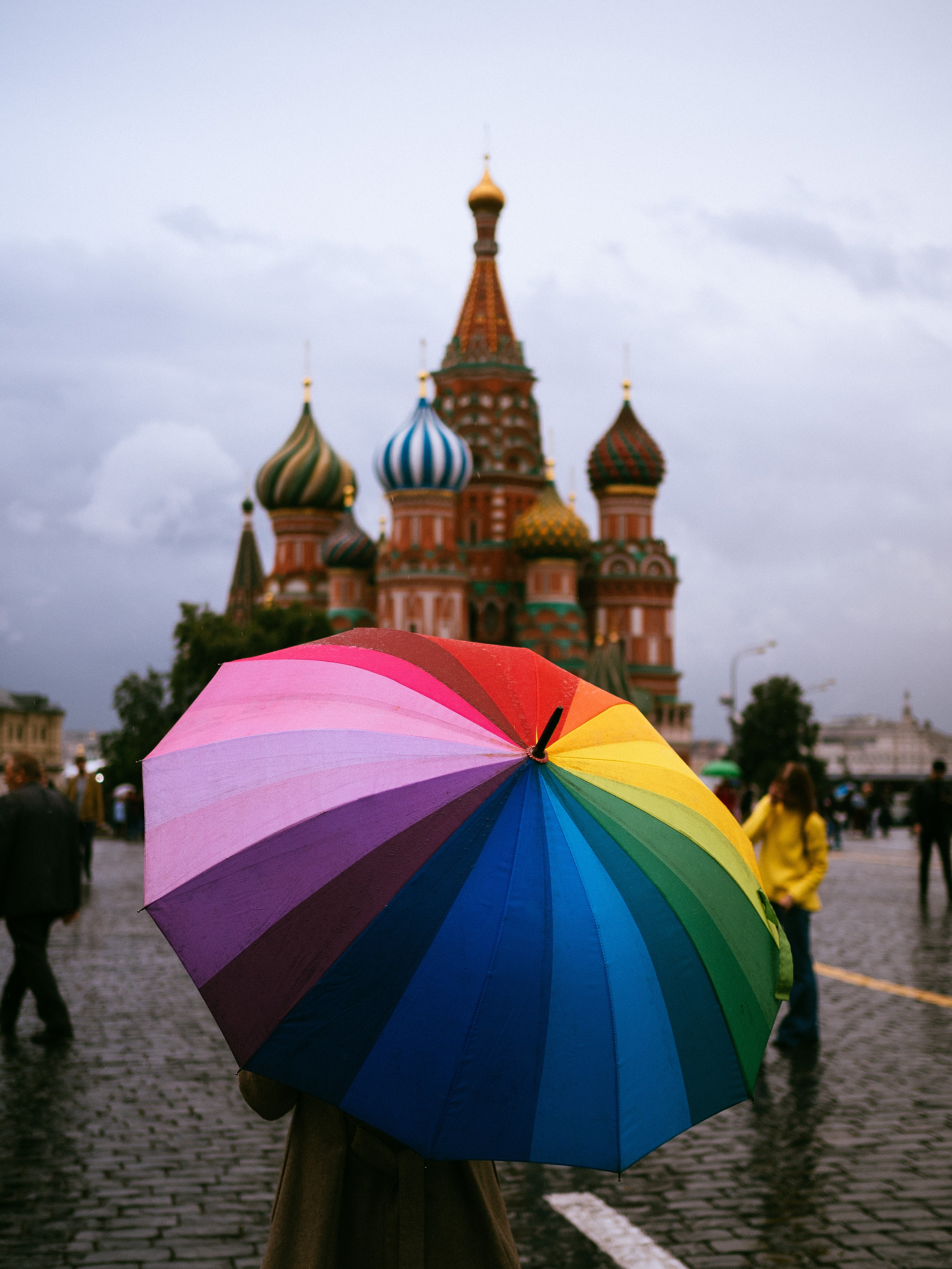 person holding rainbow umbrella in-front of Saint Basil's Cathedral, Moscow, Russia