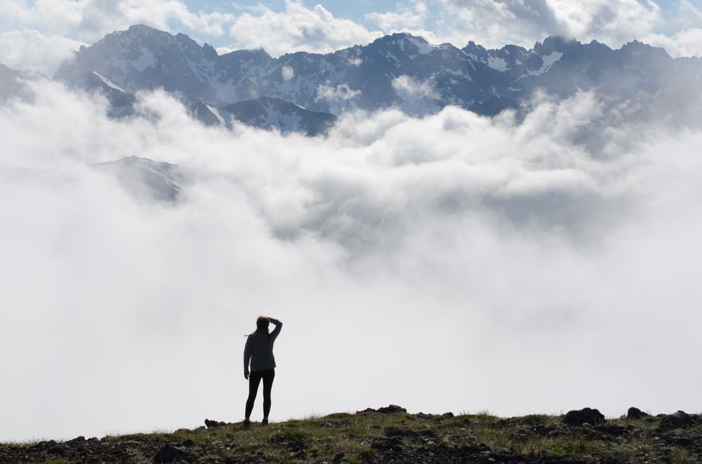 person standing on top of mountain with sea of clouds during daytime