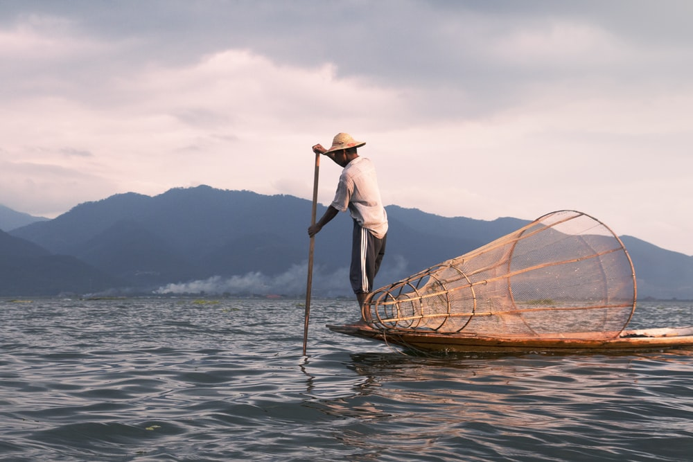 man wearing white top paddling using with his boat