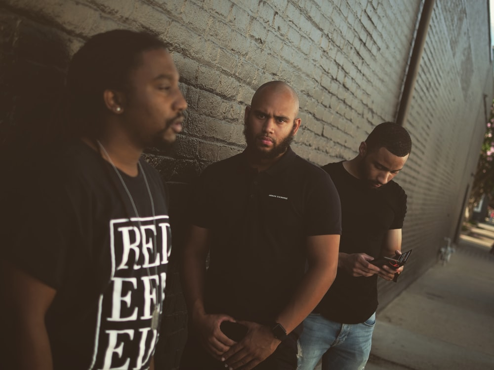 three men standing near wall