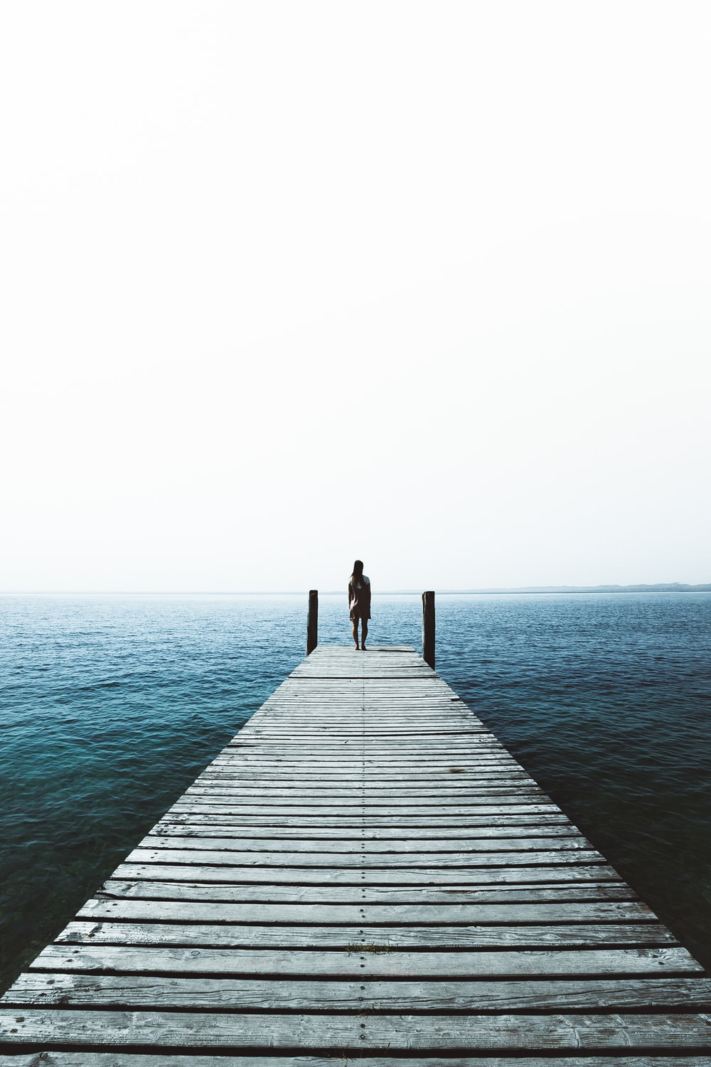 woman standing on water dock