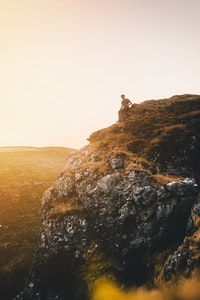 man sitting on cliff during golden hour