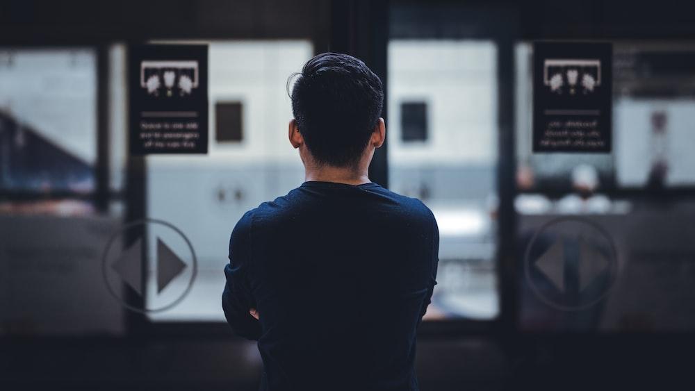 man wearing blue top facing glass door