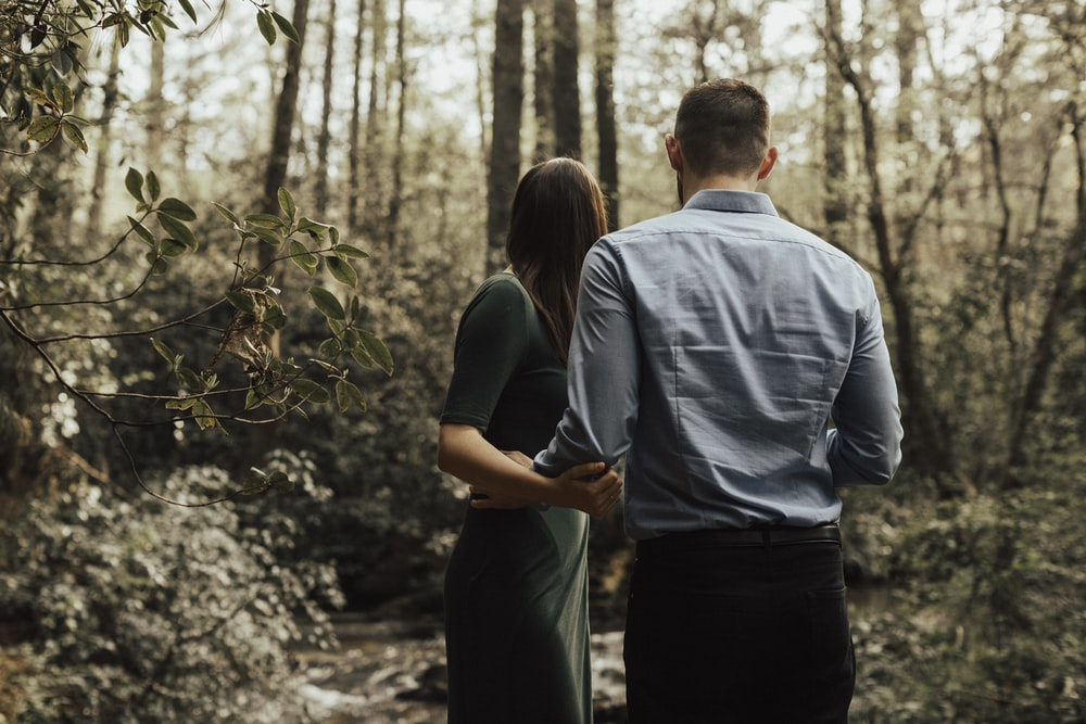 man and woman standing inside forest