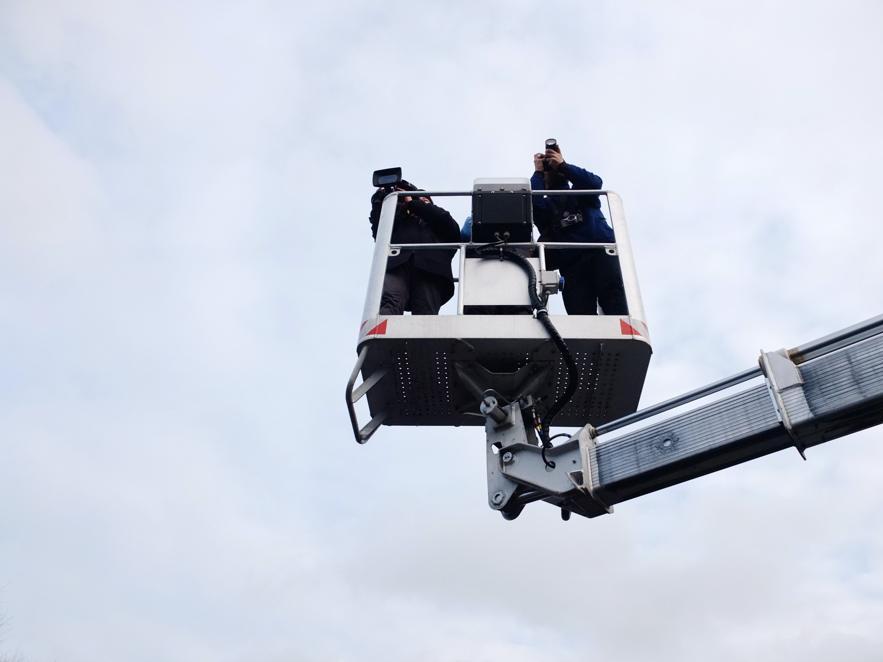 two person standing on cherry picker trailer