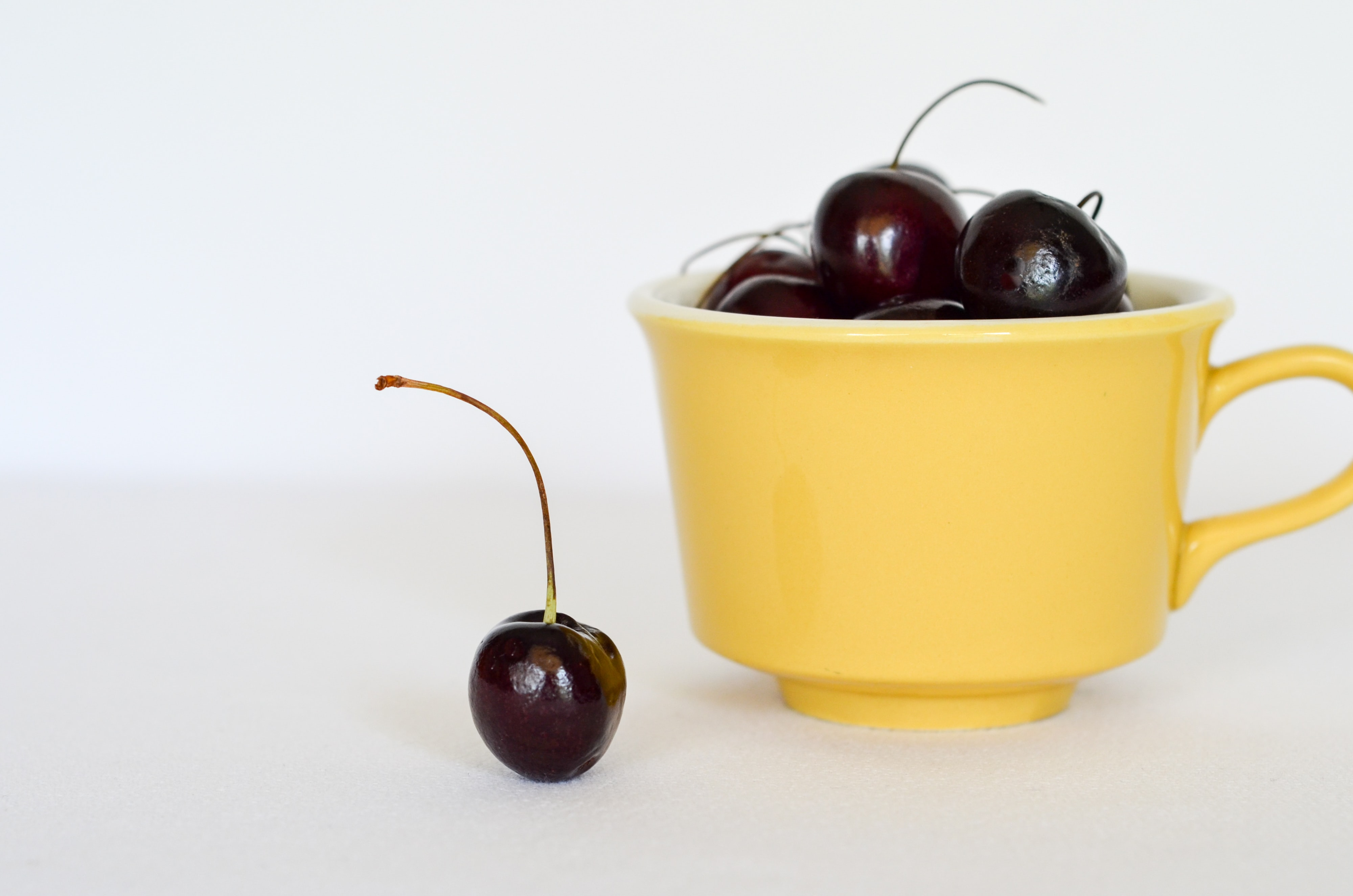 red cherry on yellow cup