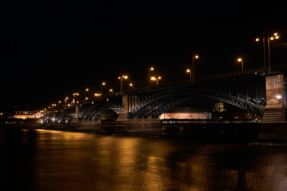 lighted metal arch bridge at night