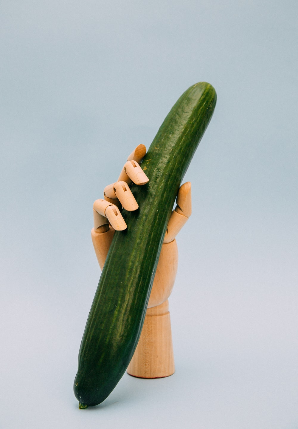 person holding green gourd with artificial hand rack
