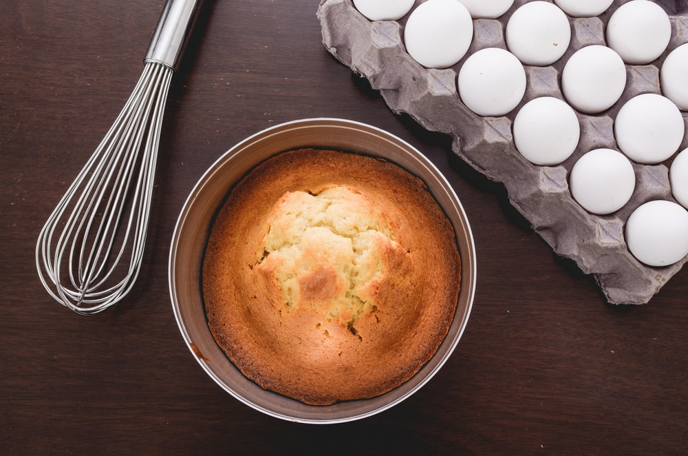 baked muffins beside tray of eggs and whisker