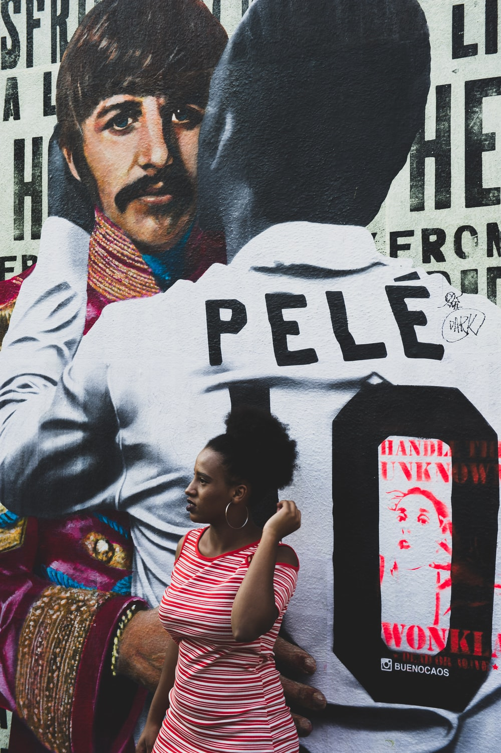 woman standing beside Pele wall