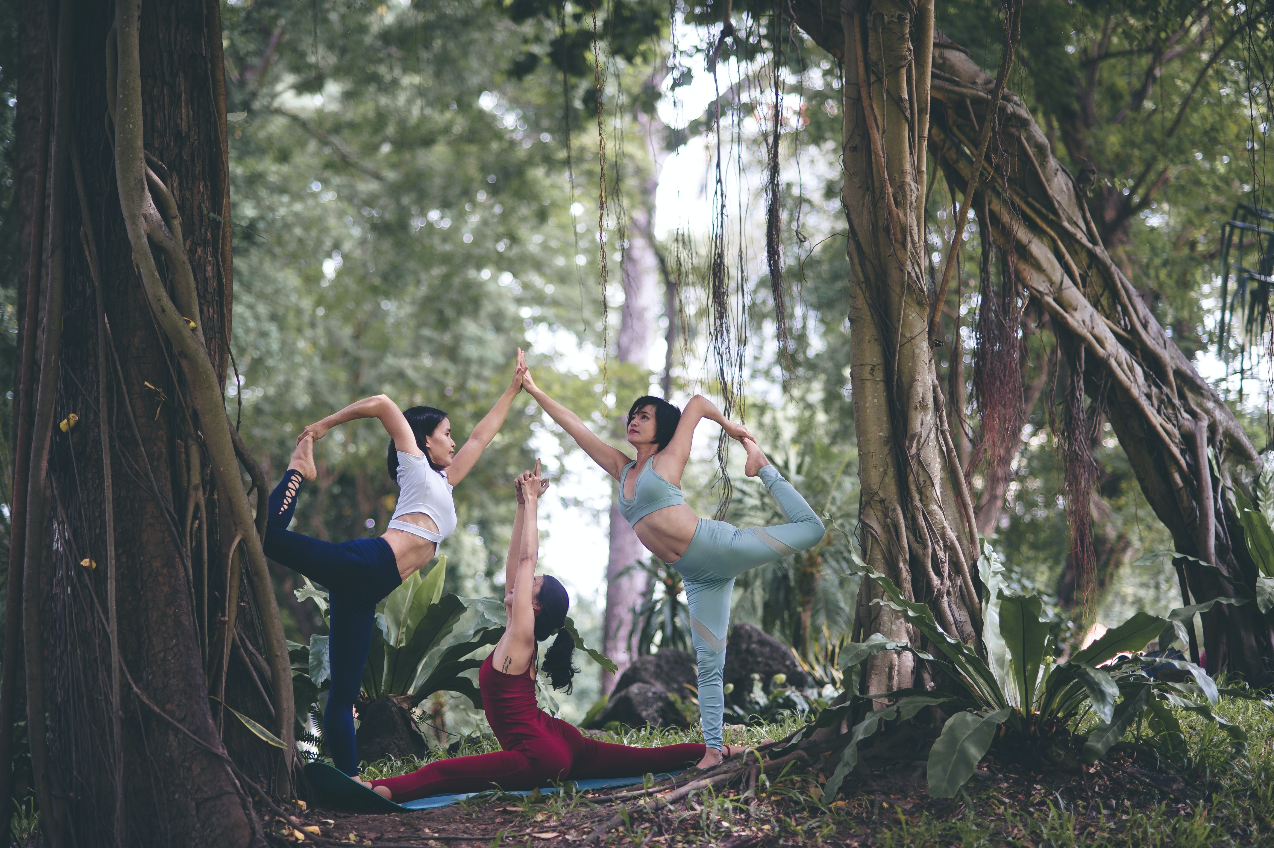 three women doing yoga at forest