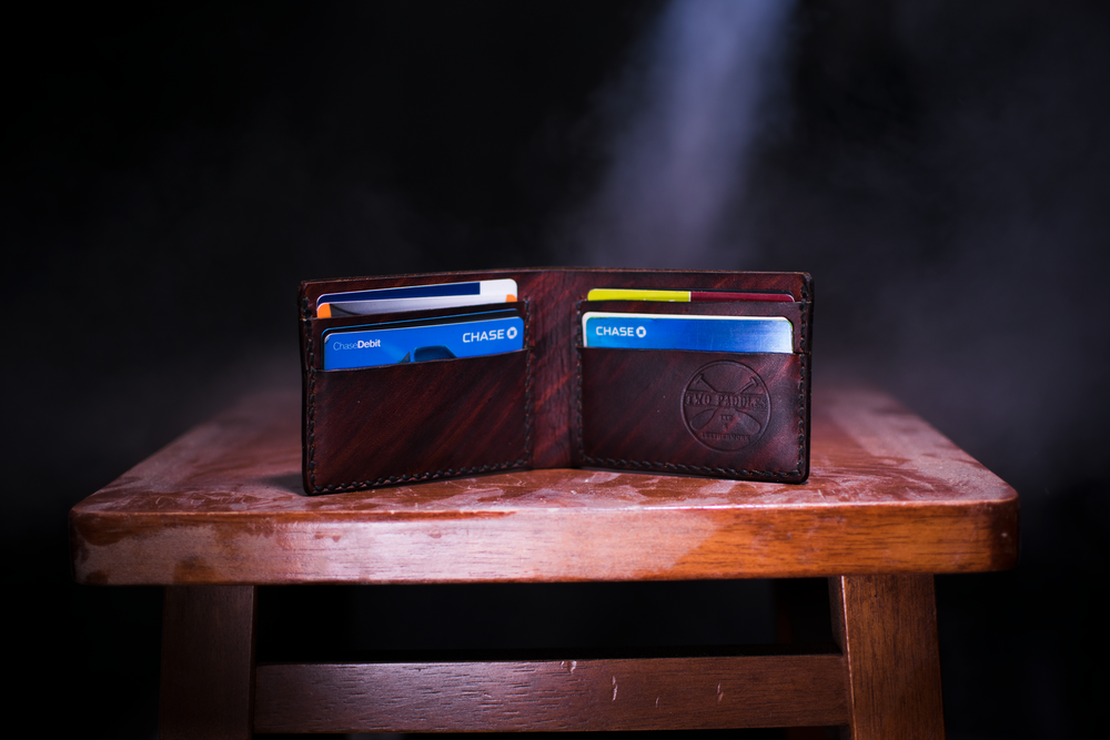 brown leather bifold wallet on table