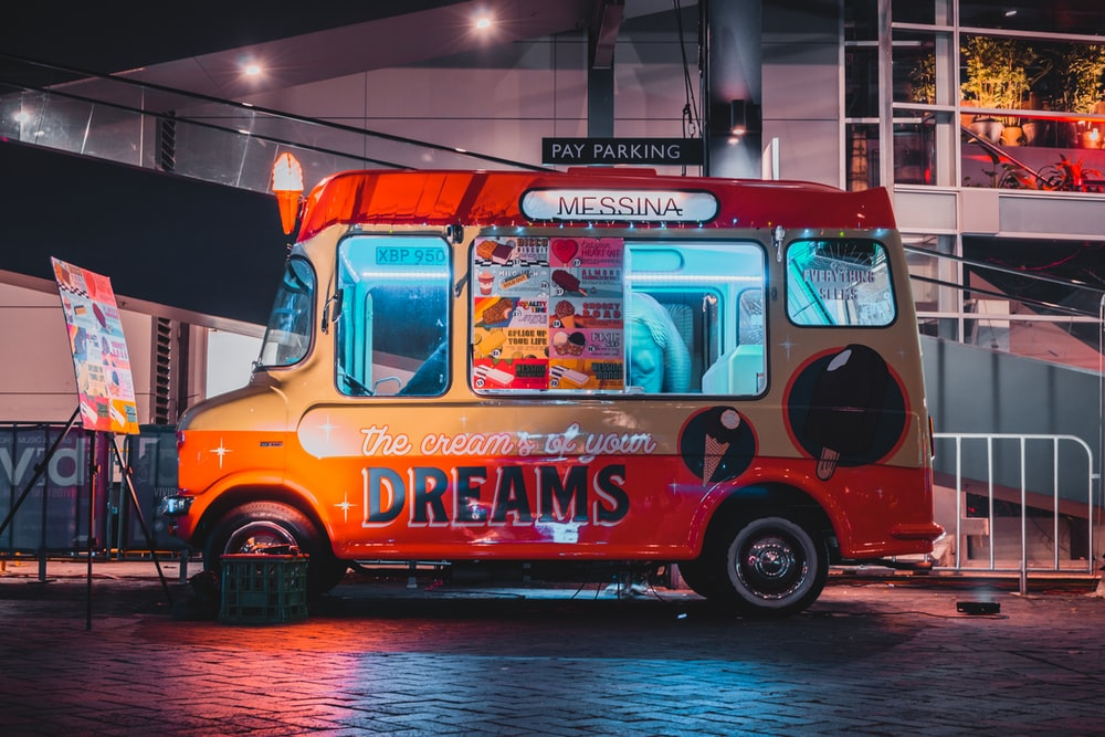 red and gray Dreams food van parked in front of building