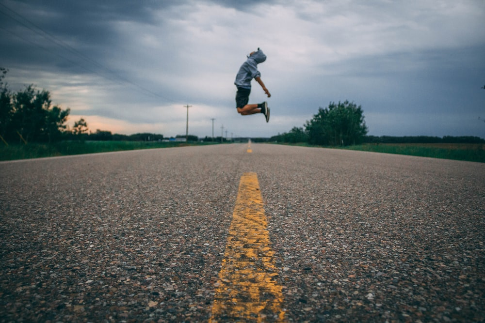 time-lapse photo of person jumping at the middle of the road