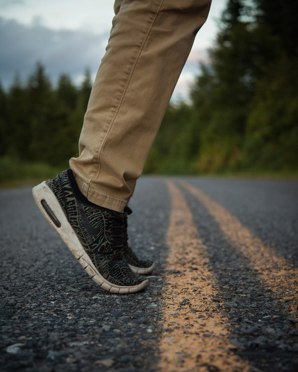 person wearing brown pants standing on road