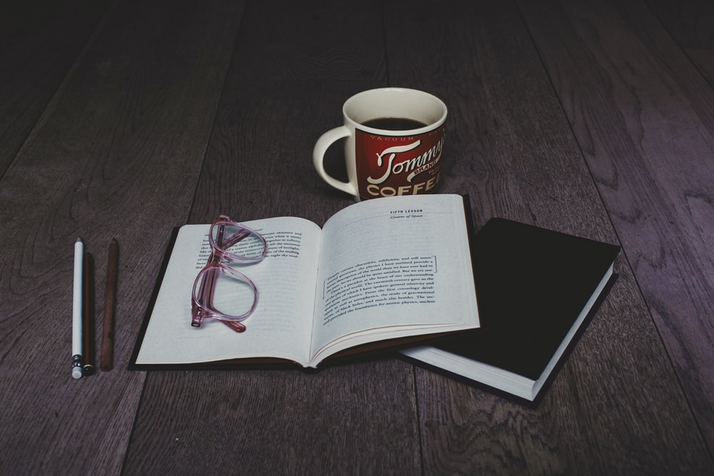clear eyeglasses on top of white book page near white ceramic mug