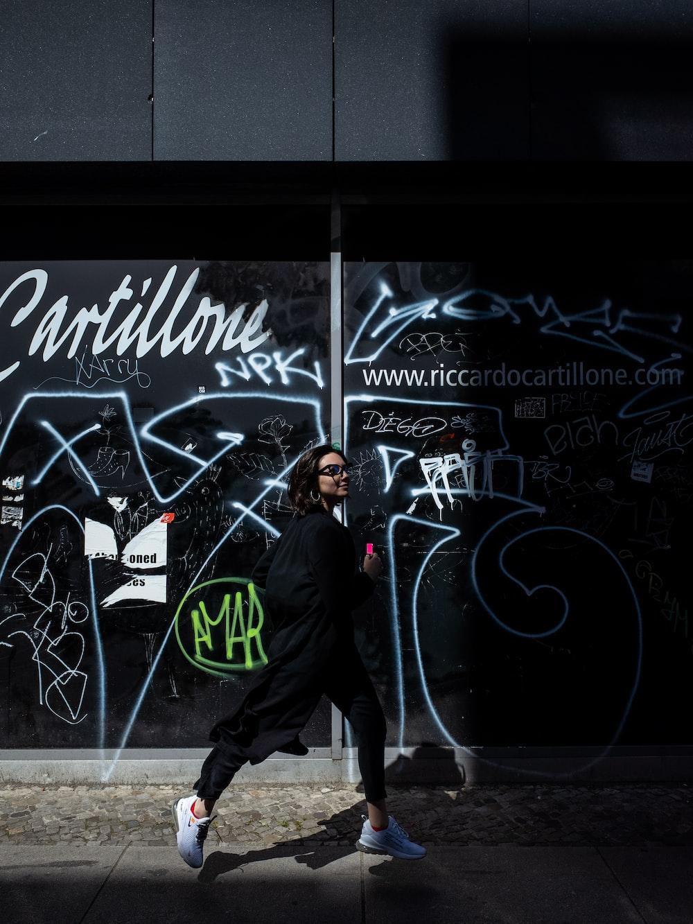 woman walking beside graffiti artwork