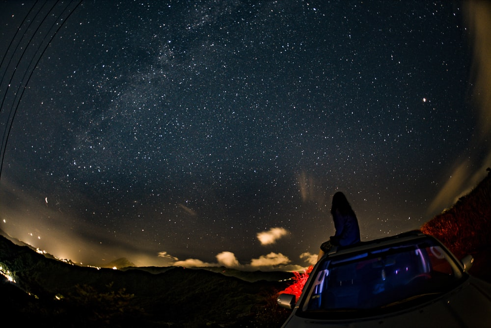 woman sitting on car while watching stars