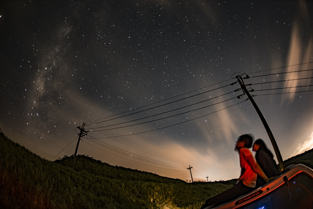 man and woman sitting on vehicle roof