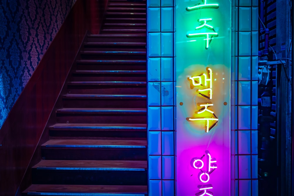 brown stair near wall with neon signage