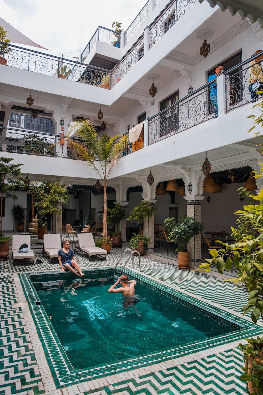 two men on pool beside three beige loungers
