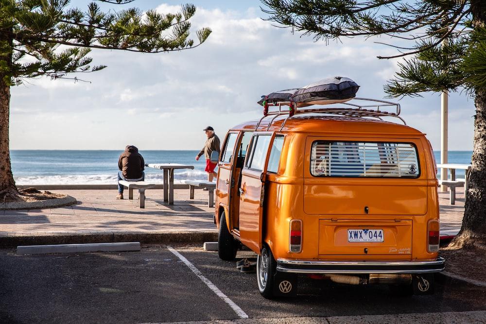 Orange van park next to the tree