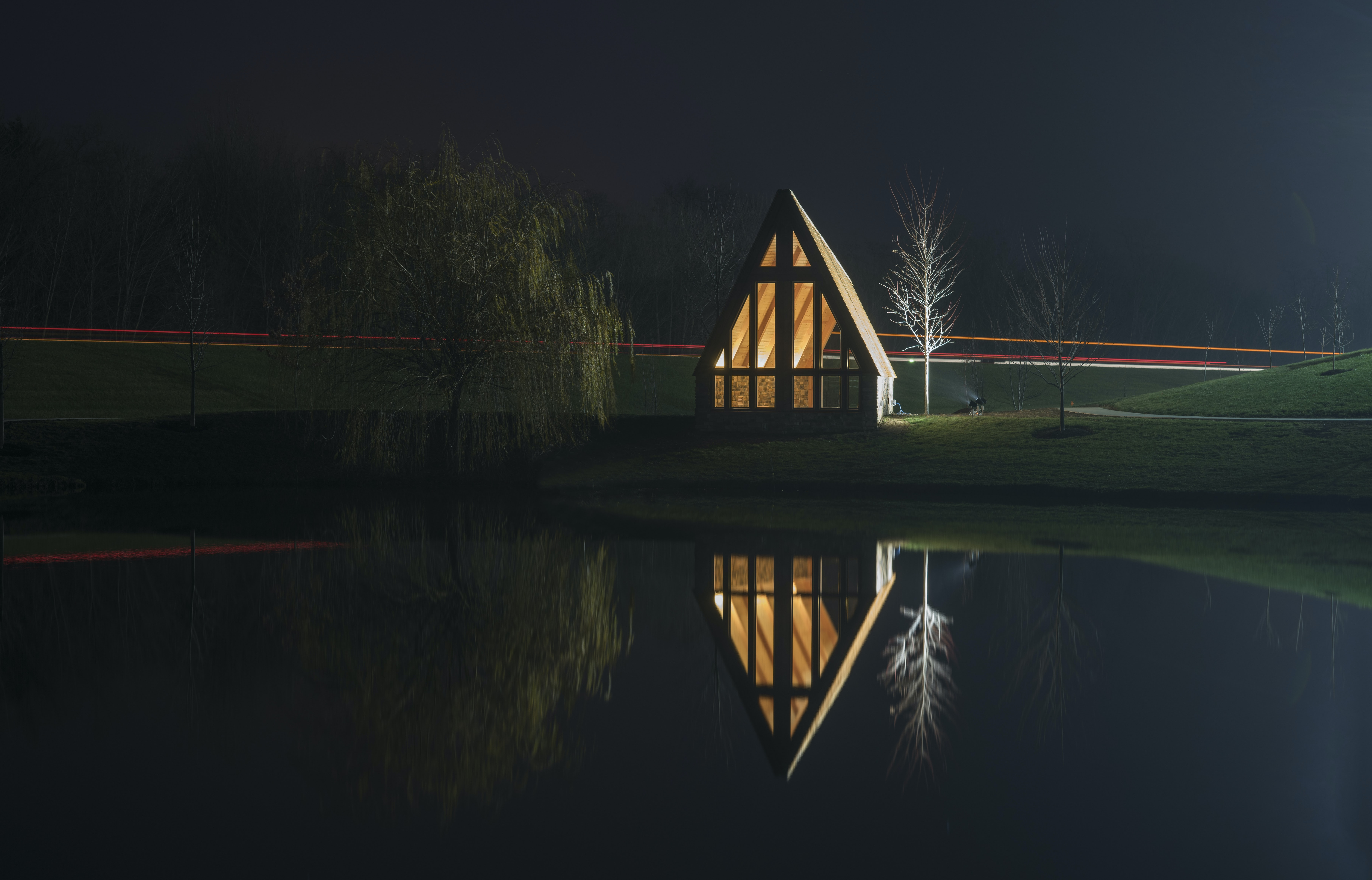 brown wooden house near bare tree with reflection on water at night time