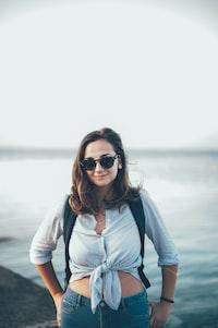 woman in blue crop-top standing beside body of water