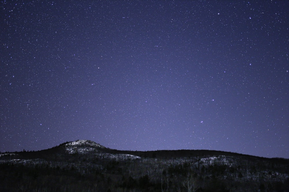 silhouette of mountain against stars
