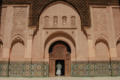 person standing on opened door of building morocco zoom background