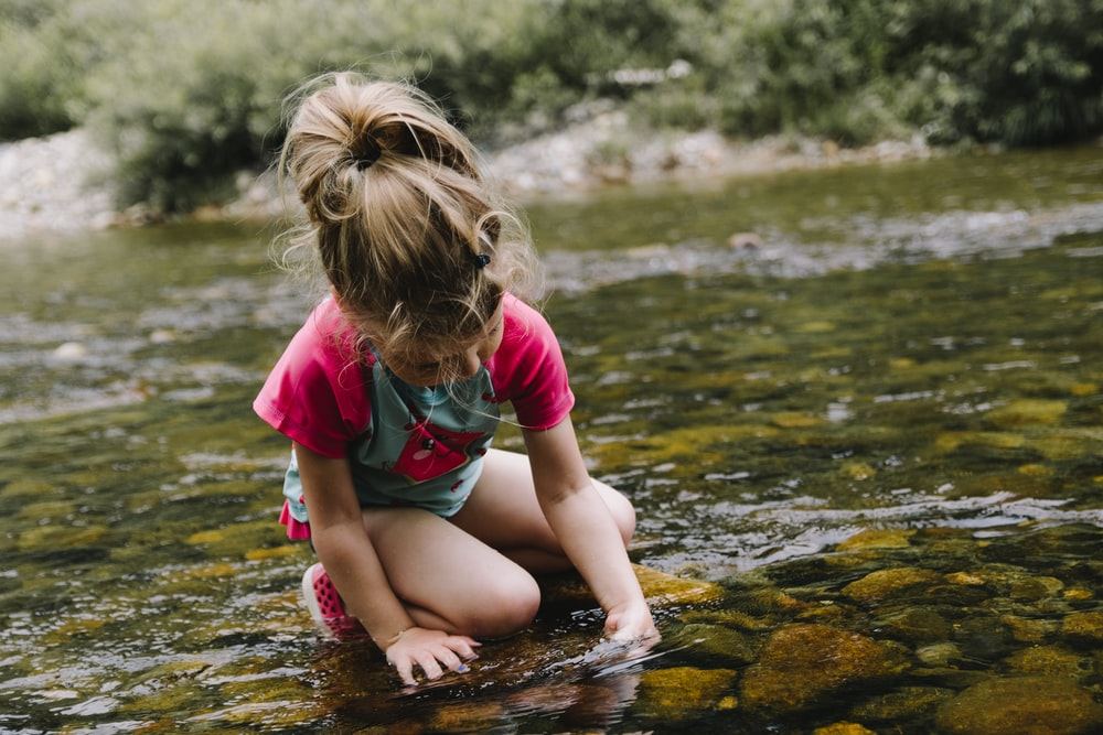 girl playing on body of water