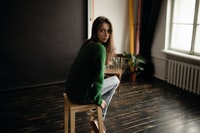 woman wearing green sweater sitting on brown wooden stool