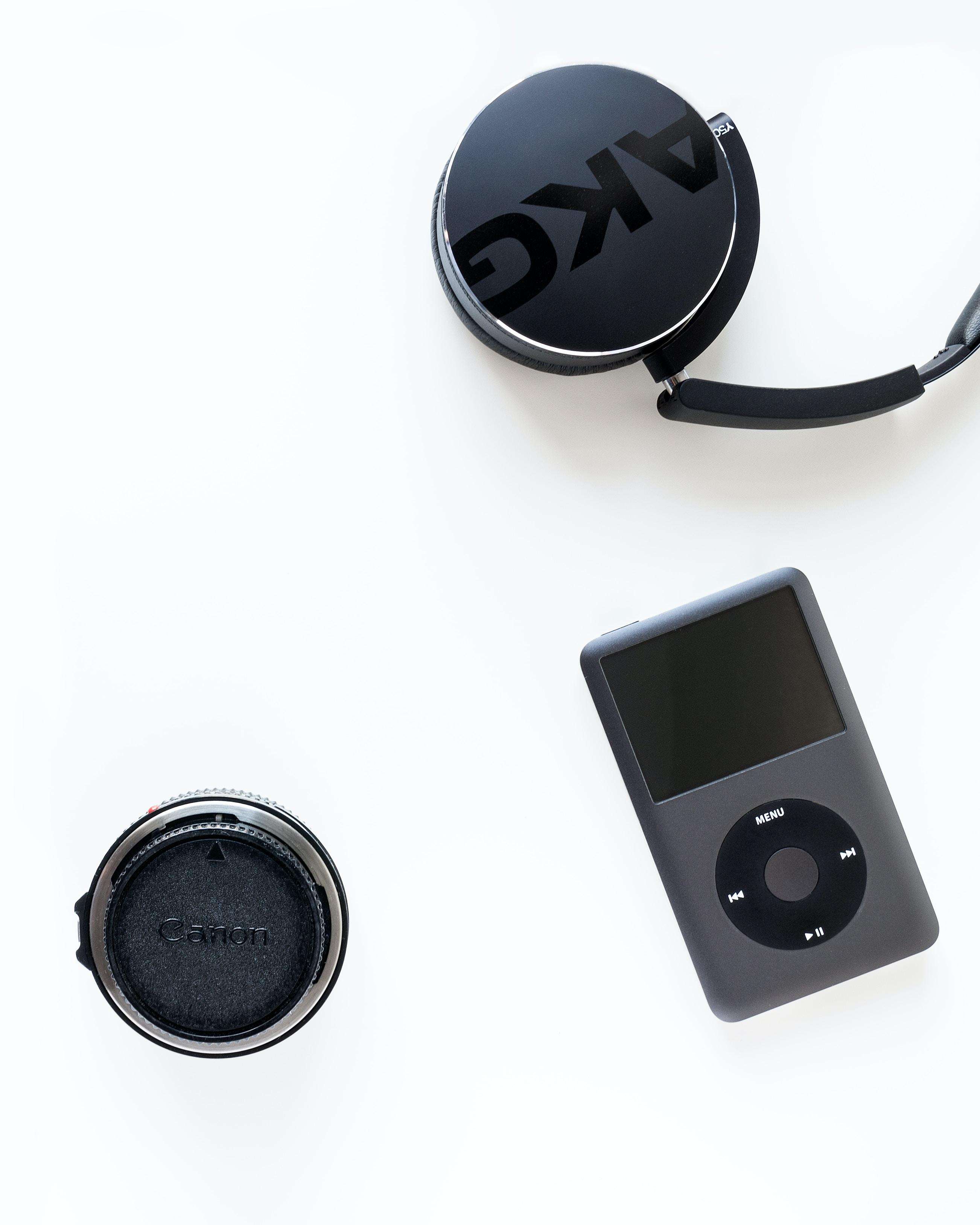 black iPod classic beside black Canon camera lens