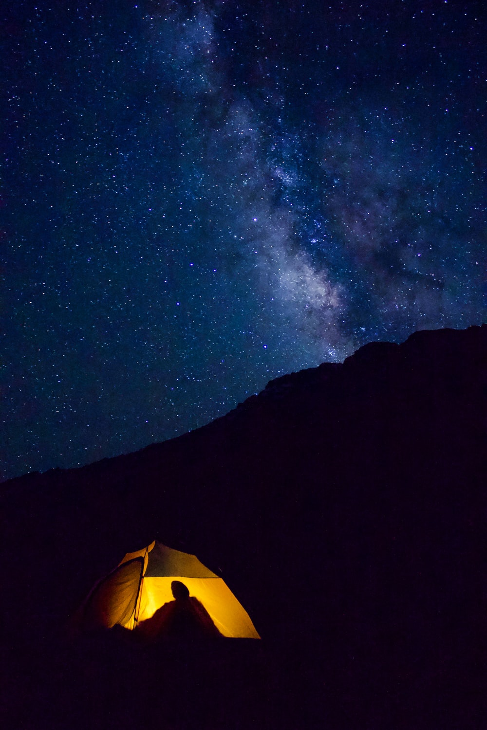 yellow lighted camp within mountain range during nighttime