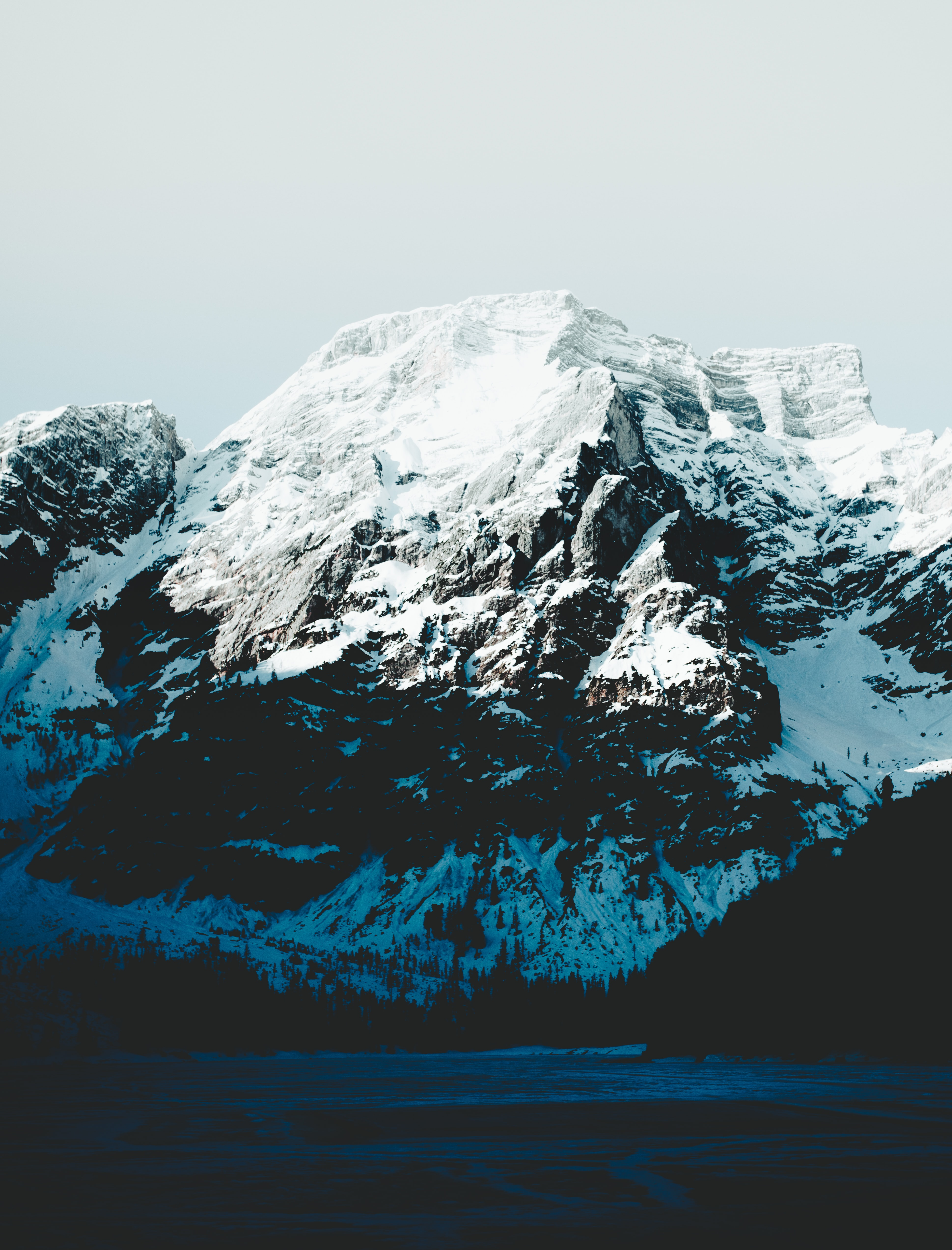 snow-capped mountain under gray sky