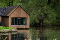 brown wooden cabin near river at daytime