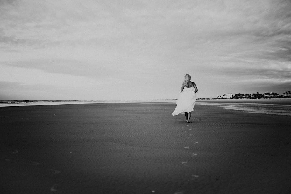 grayscale photo of woman walking on seashore