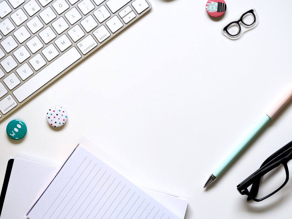 note paper, blue pen, and eyeglasses on white surface beside keyboard