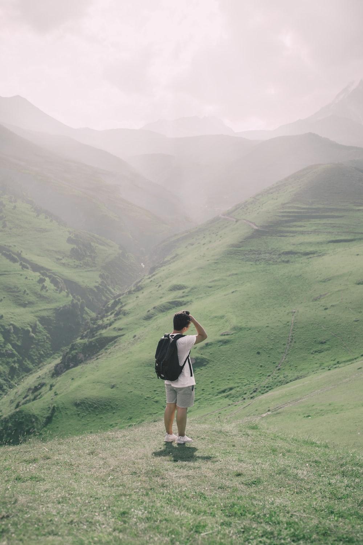 man standing on green mountain
